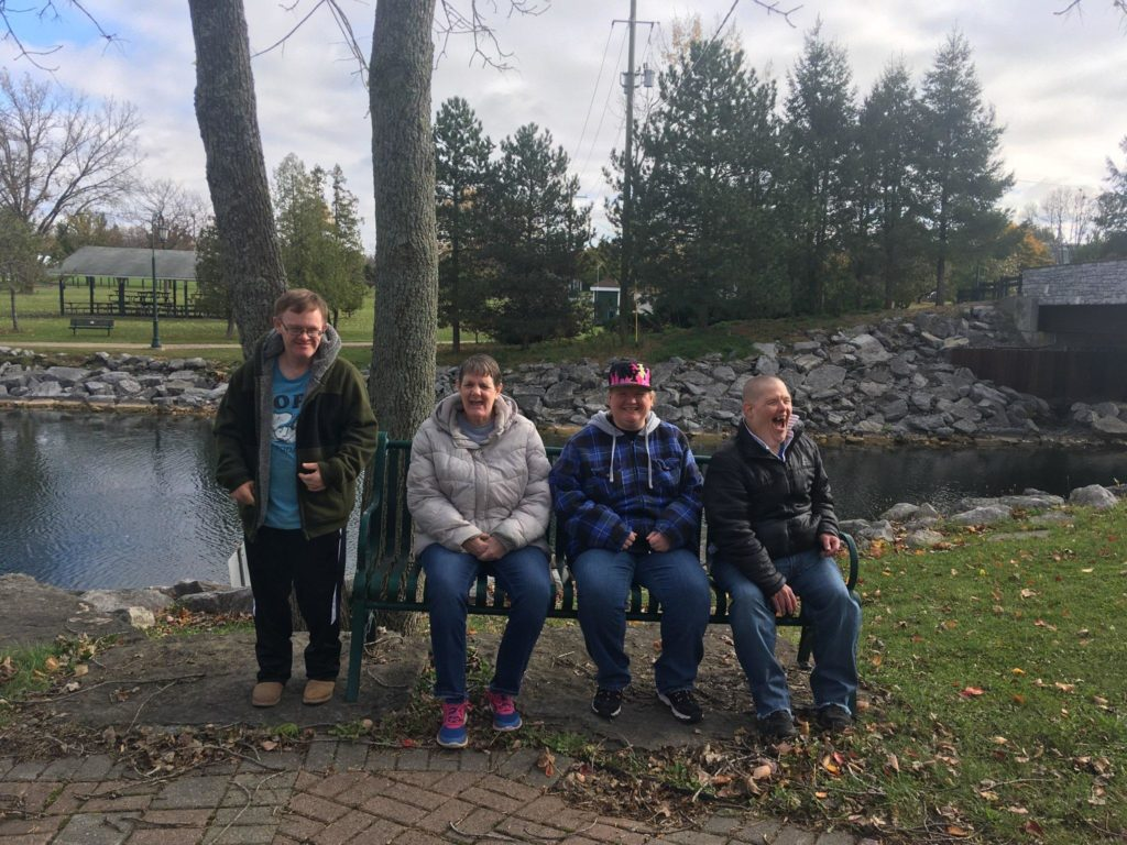 Four people with disabilities sitting on and standing next to a park bench