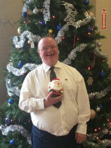 A man with disabilities holding a santa figurine and smiling in front of a Christmas tree