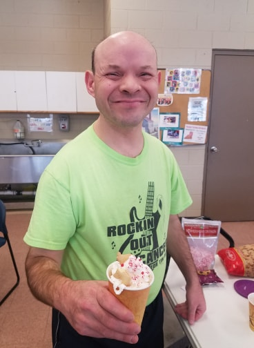A man with disabilities smiling and holding a cup of hot cocoa with whipped cream and sprinkles on top