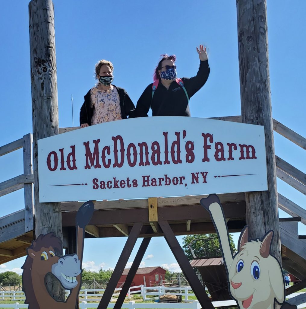 """Two adult women with disabilities standing on a bridge with a sign hung from the front. The sign says, """"Old McDonald's Farm, Sackets Harbor, NY."""" One of the two women is waving to someone off-camera to her left."""