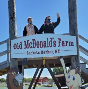 """Two women with IDD are standing on a bridge. In front of them is a sign saying, """"Old McDonald's Farm, Sackets Harbor, NY."""" The woman to the right is waving to someone off-camera."""